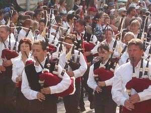 Group of young men and women, wearing white shirts (some with black waistcoats) and black trousers, marching in a parade, in the sunshine. Each is playing a bagpipe. The bag is a claret colour. The entire picture is full of people. Those not taking part in the parade are watching the procession.