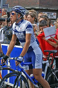 A cyclist standing over a bike while wearing a blue and white uniform.