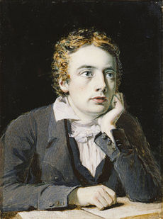 Miniature of Keats in his twenties, a pale sensitive young man with large blue eyes looking up from a book on the table in front of him, with his chin on his left hand with his elbow. He has tousled golden-brown hair parted in the middle, and wears a grey jacket and waistcoat over a shirt with a soft collar and white cravate tied in a loose bow.