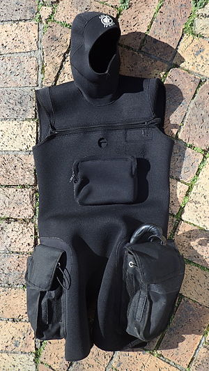 Sleeveless tunic in thin but abrasion resistant neoprene, with integral hood, two cargo pochets on the sides of the thighs, cross-chest zip closure, front pocket on the torso and opening for access to a dry-suit inflation valve. The tunic is suitable for wearing over most one-piece wetsuits for extra insulation, but mainly to support the cargo pockets and hood.