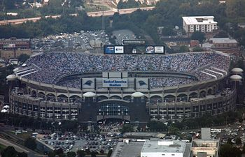 Aerial shot of an open air stadium during a football game. The outside facing is defined by a series of arches, and scoreboards are visible at the top of the facility.