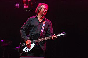 Peter Buck playing guitar and smiling