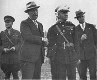 Five men, two in the foreground and three in the background, one mostly obscured. Two men are in suits and three are in their military dress uniforms. All of the men in the picture are wearing hats. The two men in the foreground are shaking hands.