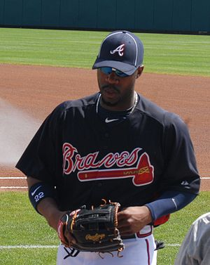 Jason Heyward on a grassy field, wearing a Braves uniform and holding a baseball glove