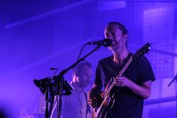 Thom Yorke playing guitar and Nigel Godrick performing