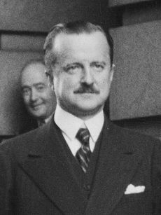 Head and shoulders of well-dressed middle-aged man with small moustache