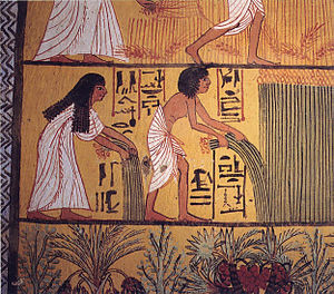 Two black-haired Egyptian peasants dressed in white-colored linen garb, standing in a field while collecting papyrus plants, with a motif of green vegetation at the bottom, and cut-off lower portion of another scene with peasants in a field at the top