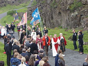 A crowd of people walking along an outdoor path. They are led by individuals in robes, and a number carry flag banners.