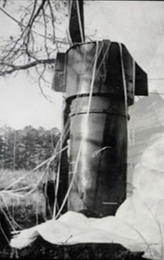 A big metallic cylinder standing upright in a field next to a tree
