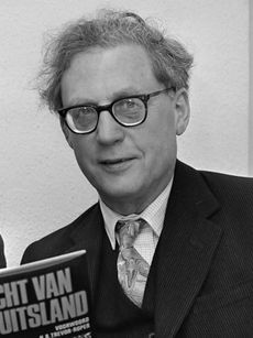 A black-and-white photograph of a grey-haired and spectacled man in his sixties is looking at the viewer. He wear a dark suit and tie, and is holding a copy of one of the books he has written.