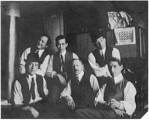 A black and white photograph of six young-to-middle-aged men, all wearing white shirts, dark ties and waistcoats.