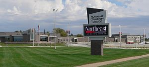 """Northeast Community College"" sign on lawn in foreground; low wide-spreading building of fairly recent design behind it"