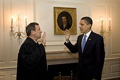 Obama (right) faces man in judge's robe as they raise their right hands