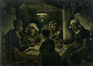 group of five sit around a small wooden table with a large platter of food, while one person pours beverages from a kettle in a dark room with an overhead lantern