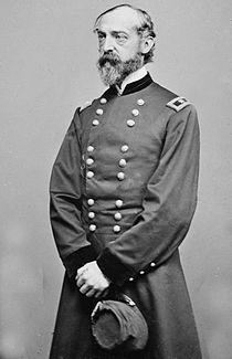 Photo of a balding and bearded George Meade in a military uniform. The somewhat thin figure is standing while holding a kepi.