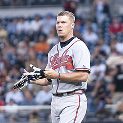 Chipper Jones, wearing an Atlanta Braves uniform, taking off his batting gloves