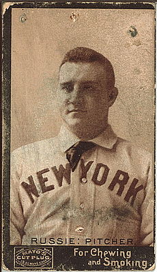 A baseball player is seen from his chest up, facing slightly left of the camera.