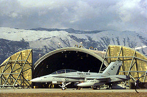 An F/A-18D on the parking ramp in front of an armored hangar in Aviano Air Base