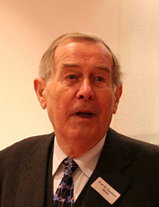 A man in his eighties with thin grey hair, facing to the right of the viewer; he wears a dark suit and tie.