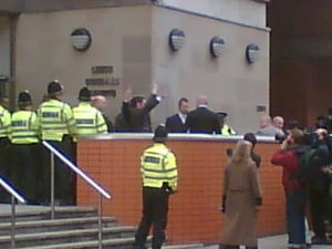Two suited men wave from behind a red brick wall, at the top of a short flight of steps leading to a grey building. Several police officers are in attendance.