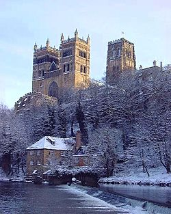 A winter view showing Durham Cathedral with three large towers looming high on a craggy cliff above a river bordered with snow-covered trees, a weir and a house.