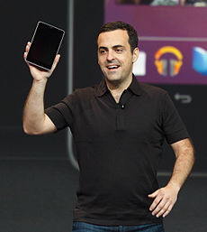 Smiling white man wearing black T-shirt holding a black rectangular device in his right hand.