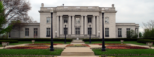 A pillared, two-story, gray marble building with several flower gardens in front