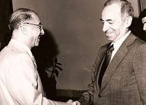 Black-and-white photo of two men in suits, shaking hands