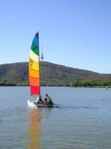 Catamaran with two adults and a child aboard. It has a rainbow-coloured horizontal striped sail. The water is calm and empty and Telstra Tower is in the background.