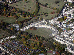 Aerial photograph of semicircular terrace of stone buildings with large expanse of grass in front and to the left. Also shows surrounding terraces of buildings.