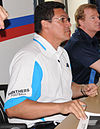 Sitting at a table, a man wearing a white Panthers shirt and glasses is signing an autograph.