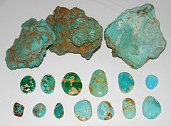 Three rough chunks of raw turquoise in brown matrix are at the top of the picture, below which are a range of thirteen finished cabochons showing various colors ranging from green to light turquoise blue, and a range of spiderweb matrix ranging from none to light yellow to deep brown.