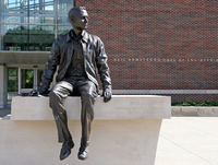 "Photo of a statue of Neil Armstrong sitting on a ledge. The words ""Neil Armstrong Hall of Engineering"" are visible on the building in the background."