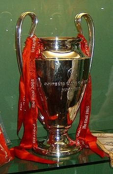 A silver trophy with red ribbons on it, set against a green background