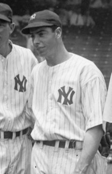 "A man stands in a line. He is wearing a white uniform with stripes and a black baseball cap, which both have an interlocking ""N"" and ""Y""."