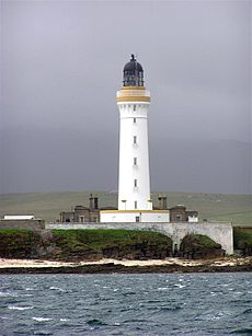 A tall white lighthouse with a brown stripe around the parapet and dark coloured lantern sit on a rocky shore. A white wall obscures the lower floor of grey stone buildings gathered around its base.