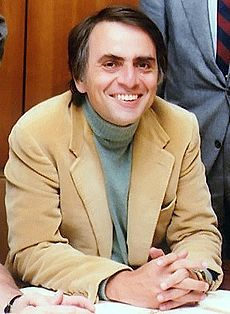 A middle-aged man sits at a desk, wearing a casual jacket and jumper. He is smiling and holding his hands together to pose for a photograph; this is physicist Carl Sagan.
