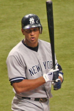 "A man in a baseball jersey and batting helmet. His helmet is emblazoned with a white ""N"" and ""Y"" intertwined, and ""NEW YORK"" is stitched in black letters across his button-down jersey. The player is holding a black baseball bat almost vertically with black, gray, and white gloves."