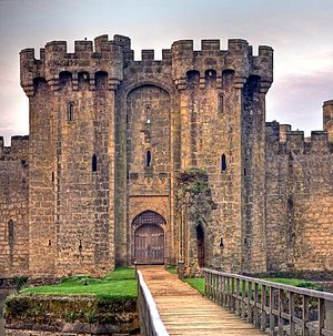 Photo of the main entrance which shows a large door recessed in a double archway in which there is a portcullis. The entrance is set in a tall battlemented gatehouse framed by twin towers with machicolations and slits. The entrance is approached by a bridge