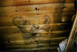 A wooden planked wall on which can be seen a stylised drawing of a woman's head and other ornamental shapes and objects
