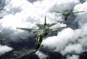 Front view of two jet aircraft in two-tone green camouflage scheme in-flight, wings unswept. The trailing aircraft is slightly off-centered to the right