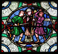 A detail from an ancient stained glass window shows Becket being murdered by several men.