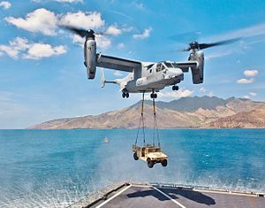 A MV-22 with its rotors up to vertical with a HMMWV vehicle hanging by two sling wires.