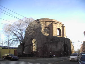 Exterior of a ten-sided ruin called today the Temple of Minerva Medica at the intersection of city streets in Rome showing large arched windows in the drum between engaged buttresses and below polygonal step-rings buttresses for the collapsed dome