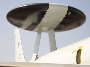 Close-up view of black disc-shaped radar with wide diagonal white band. The radar rests on two convergent struts above aircraft fuselage.