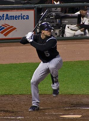 A man in a black baseball jersey and gray pinstriped pants prepares for a right-handed baseball swing.
