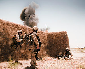 Marines beside a mud wall as an explosion goes off behind it