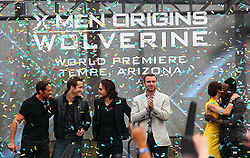 "Atop a stage are three man in black clothing, Liev Schreiber wearing a gray jacket and black pants, and Lynn Collins, wearing a yellow dress, hugging will.i.am, who is in black clothing. In the background is a billboard reading ""X-Men Origins Wolverine: World Premiere – Tempe, Arizona. Colored paper flies through the stage."