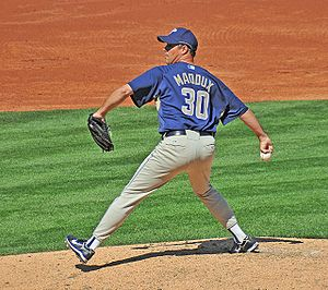 "A man wearing a blue cap, blue top and light colored trousers, holding a baseball. The back of his shirt reads ""Maddox 30"""