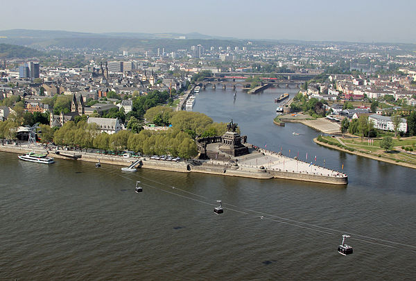 high angle view the confluence of two major rivers, marked by the statue of a man on a horse, with a city behind